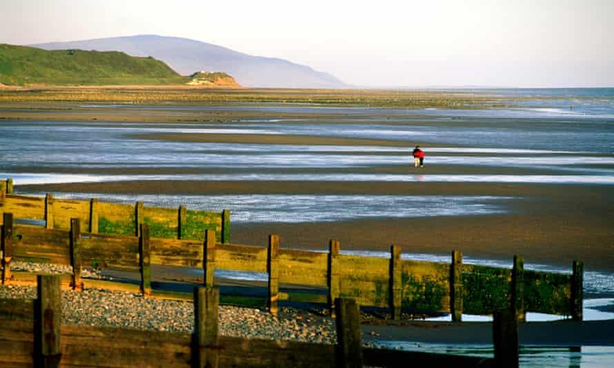 A couple walk on the beach at St Bees Head, near Workington, Cumbria.