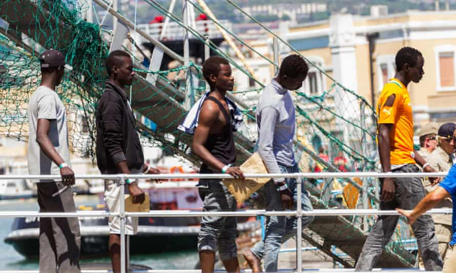 Rescued migrants disembark from the Siem Pilot at Catania.