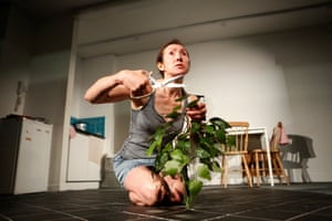 Pauline Knowles as Jane and an apple sapling sprouting in the climate-change wasteland kitchen of The Garden at the Traverse.