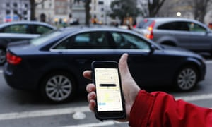 Person holding mobile phone with uber app