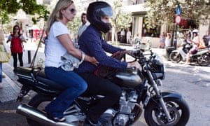 Varoufakis leaves on his motorcycle with his wife Danae Stratou after resigning on 6 July 2015