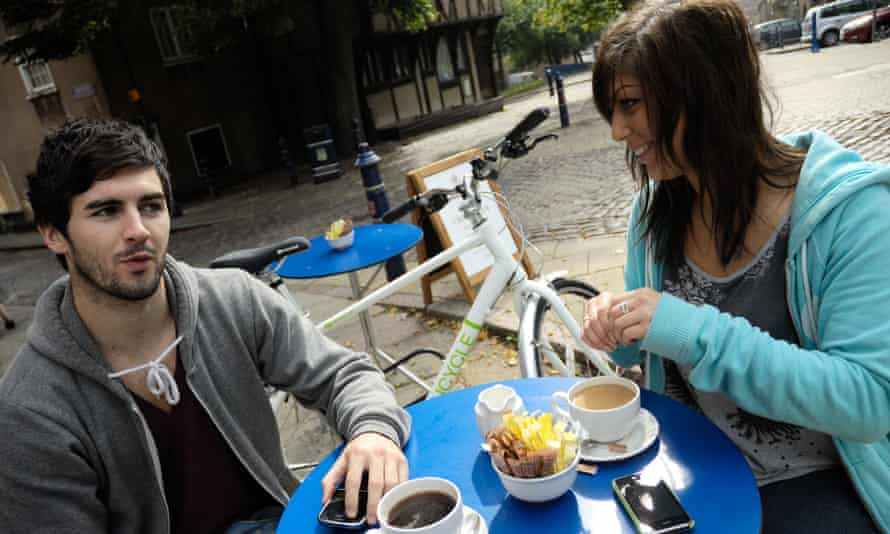 A couple enjoy a coffee with their bikes nearby