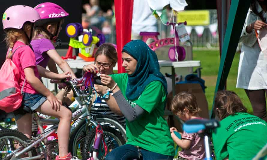 Volunteers help two children with their bikes