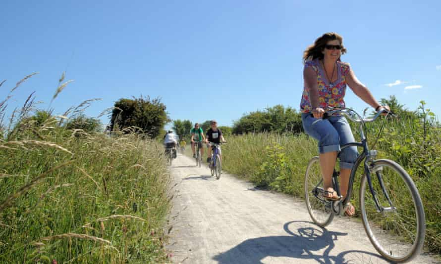Woman cycles on a chalk path through the countryside