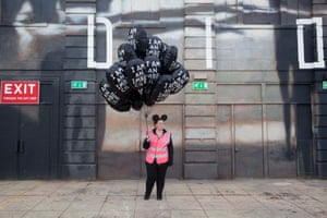 A security person holds balloons reading 'I am an imbecile'