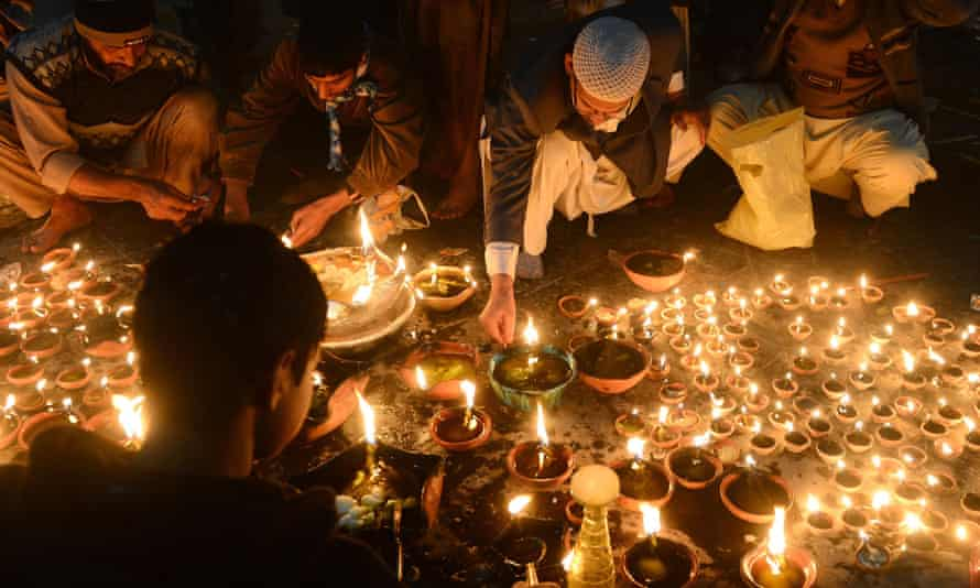 Devotees light candles at the shrine of Muslim Sufi Saint Data Ganj Bakhsh in Lahore. Photograph: AFP/Getty Images