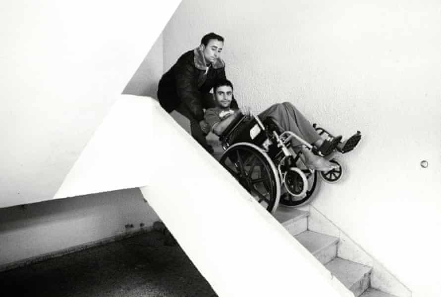 Odai is helped down the stairs by his brother Abdullah.
