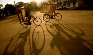 Two cyclists carrying furniture on their bicycles, in western Uganda.