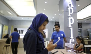 An Iranian woman tries out an iPhone in an electronics shop selling Apple products in Tehran, Iran.