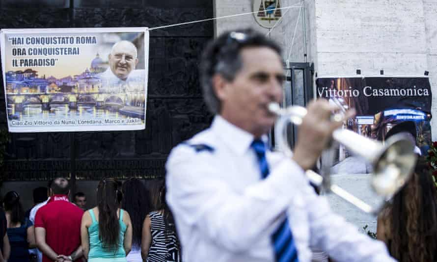 A man plays a trumpet in front of a banner showing Vittorio Casamonica and reading 'You conquered Rome, now you'll conquer paradise'.