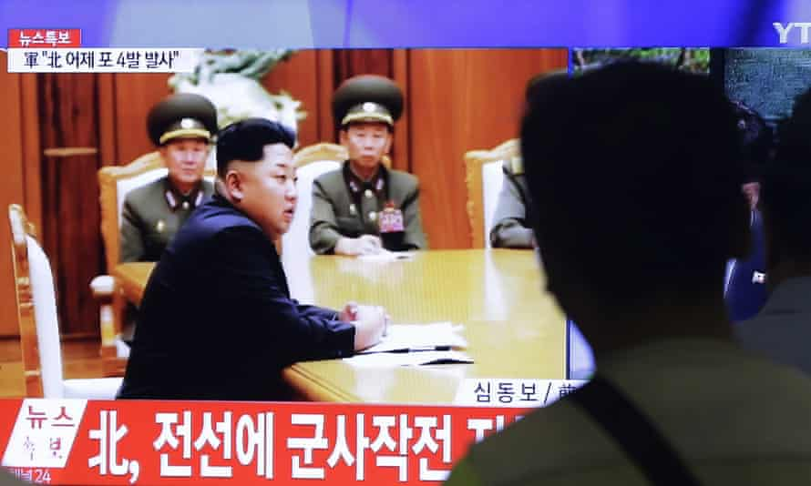South Koreans watch a television news programme showing footage of Kim Jong-un. The caption reads: 'North Korea orders military to have full combat readiness.'