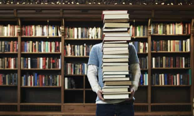 Young man carrying stack of books in university library.