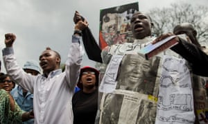 A man celebrates Nelson Mandela's life as people dance and sing outside the house of the late South African president in Johannesburg.