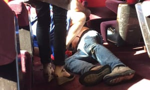 A man lies on the on floor in the train