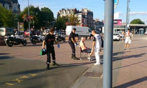 French emergency services help an injured passenger outside the station
