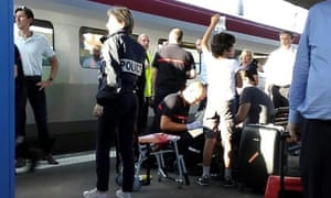 A police officer stands by as a passenger receives medical attention