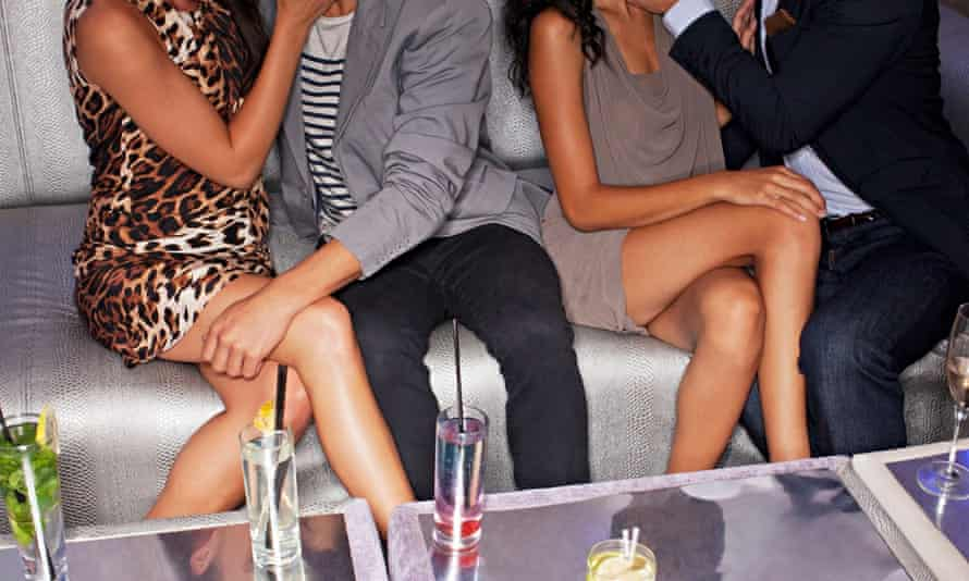 Legs of couples sitting on sofa in nightclub. Image shot 2012. Exact date unknown.