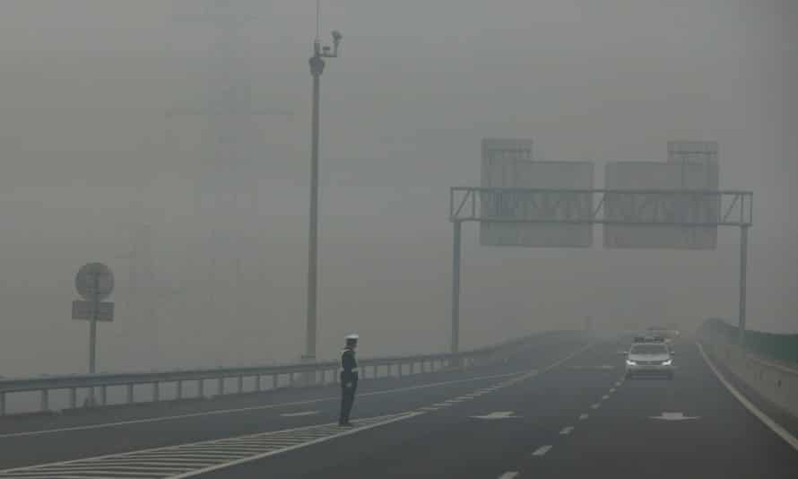 A traffic police officer standing on an expressway is barely visible due to hazardous pollution levels, in Hebei province, China, 26 November 2014.