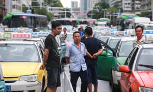 Taxi drivers driving vacant taxis in queues cause traffic jams on a road in Wuhan city, central China, as part of a protest against Uber.