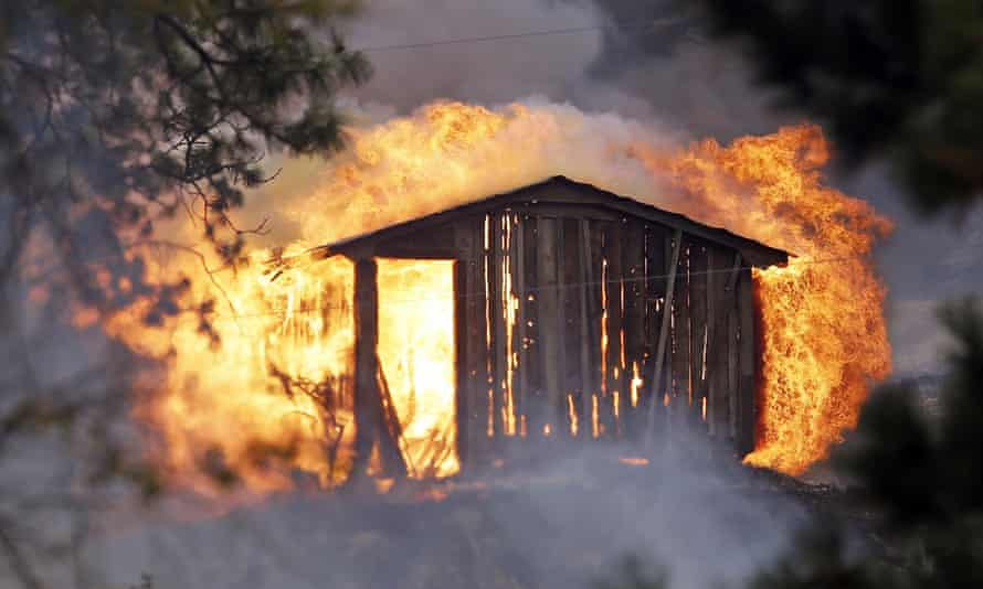 Flames pour from a structure fully engulfed in fire in a wildfire Friday afternoon in Tonasket, Washington.