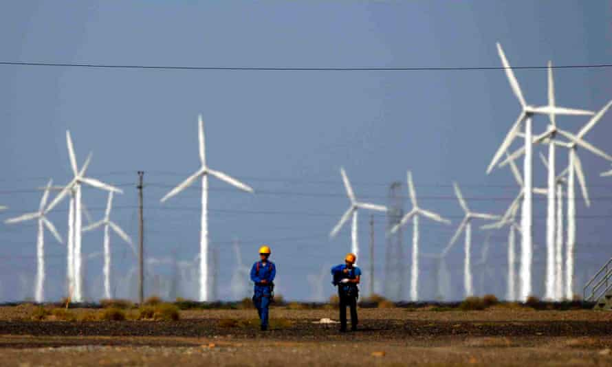 Workers walk near wind turbines for generating electricity, at a wind farm in Guazhou, China