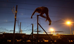 A migrant jumps a fence in calais