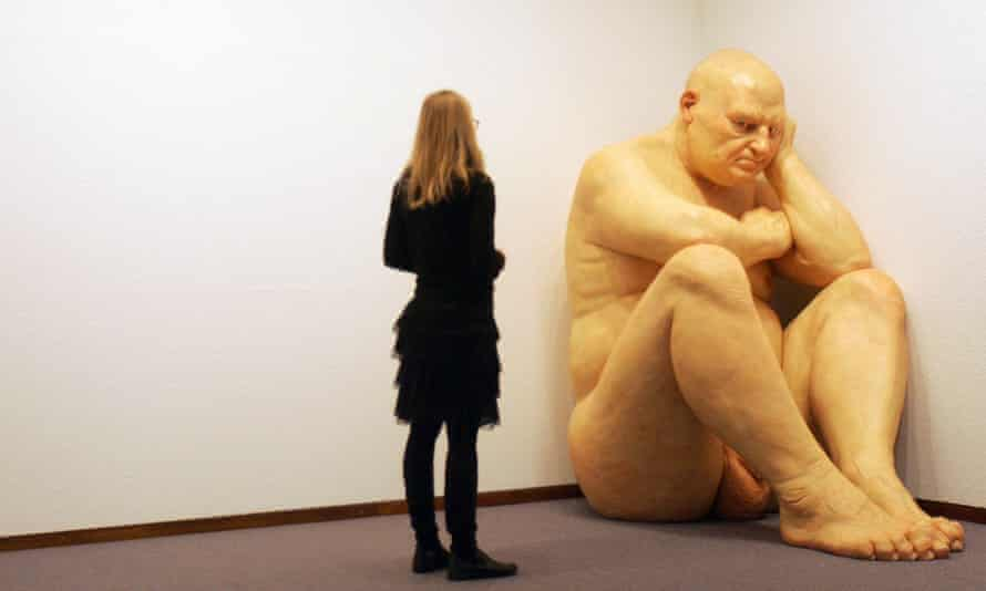 A woman contemplates the sculpture Untitled (Big Man) by Australian artist Ron Mueck in February 2006 at the Neue Nationalgalerie museum in Berlin.