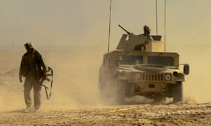 A US marine leads a Humvee as he looks for IEDs on a road near the town of al-Qaim, western Iraq, in October 2005.