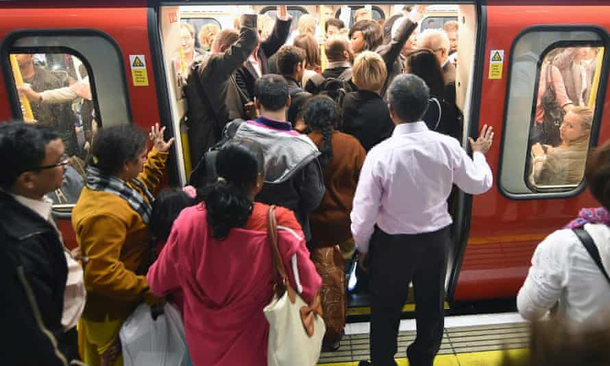 Commuters struggle to board a tube train at Westminster