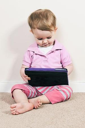 A baby girl plays on an iPad