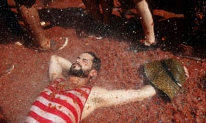 A man soaks up the atmosphere and tomato pulp as crowds throw tons of ripe tomatoes at each other.