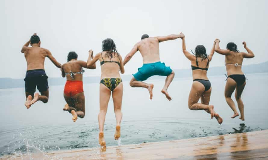 Holidaymakers jump from a jetty into the water.