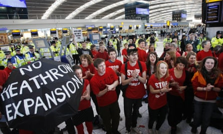 Climate change protesters chant during a demonstration inside Terminal 5 at Heathrow Airport.