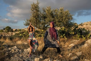 A mother and her daughter practice yoga in Palestine