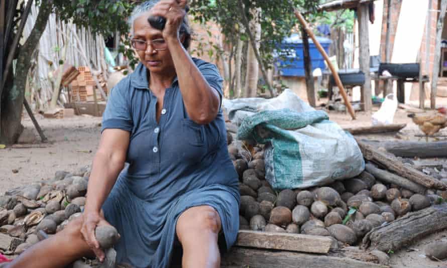 Nazare Naza breaking babassu in her backyard in Maranhao.
