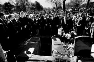The British criminal underworld, friends and family gather to pay their last respects to gangster Charlie Kray at his graveside in Chingford cemetery, Essex. His brother Reggie Kray, released from prison for the funeral that day, stands by the open grave, handcuffed to a prison officer.  In the front row of the massed crowd of mourners stands 'Mad' Frankie Fraser, former adversary of the Kray twins 'firm', now paying his last respects to his former foe.
