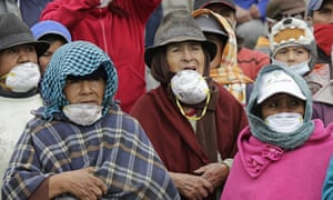 Residents wearing masks to protect their airways from volcanic ash listen to President Correa