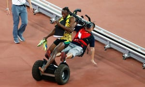 Usain Bolt gets cleaned out by a cameraman on a segway moments after successfully defending his 200m title.