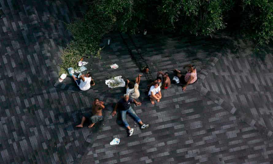 A family sitting trapped atop a roof during Katrina.