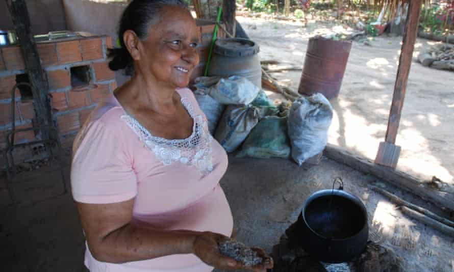 Emilia Alves da Silva Rodrigues in her backyard in Tocantins holding ground babassu seed kernels.
