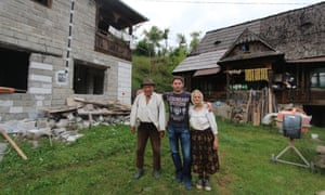 One of the Vasiles with his grandparents next to old and new houses.