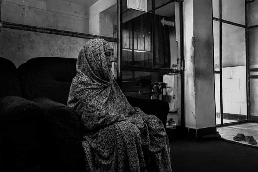 A woman waits outside Arab Shah's office for her appointment.