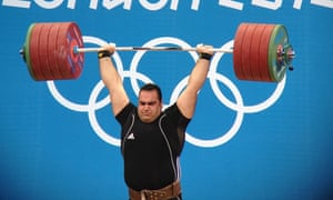 Weight lifter holds large weight above head
