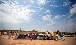 Sudanese women and children rest under shelter at a refugee camp in Darfur