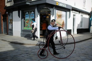 Penny farthings are wheeled through the streets