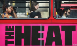 Passengers ride a bus displaying an advert for a movie entitled The Heat on July 17, 2013 in London, England.