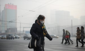 A  woman wearing a face mask makes her way along a street in Beijing