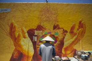 Irving Trejo paints a section of a mural