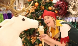 An elf poses for a photograph in the Christmas shop, at Selfridges department store on Oxford Street.