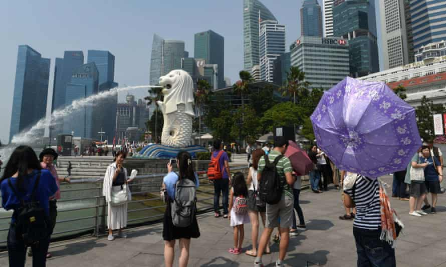 Tourists visit the Merlion statue in Singapore. The country has lifted its two-decade-long ban on visitors with HIV.